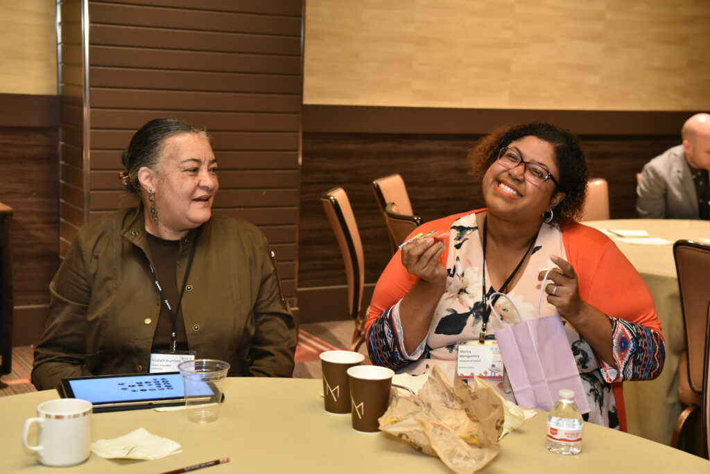 Two women seated at a table, smiling, during a break at 2018 Forum