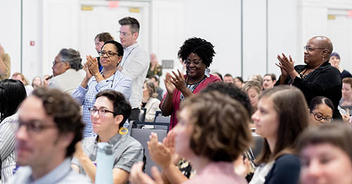 Attendees applauding and giving a standing ovation at the 2019 DLF Forum plenary