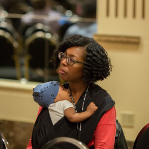 DLF Advisory Committee member Stacie Williams listens to keynote while holding infant chiild